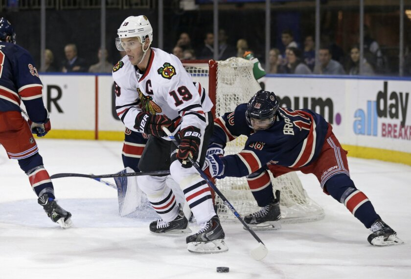 Chicago Blackhawks' Jonathan Toews (19) looks to pass as New York Rangers' Derick Brassard (16) defends during the first period of an NHL hockey game Wednesday, Feb. 17, 2016, in New York. (AP Photo/Adam Hunger)