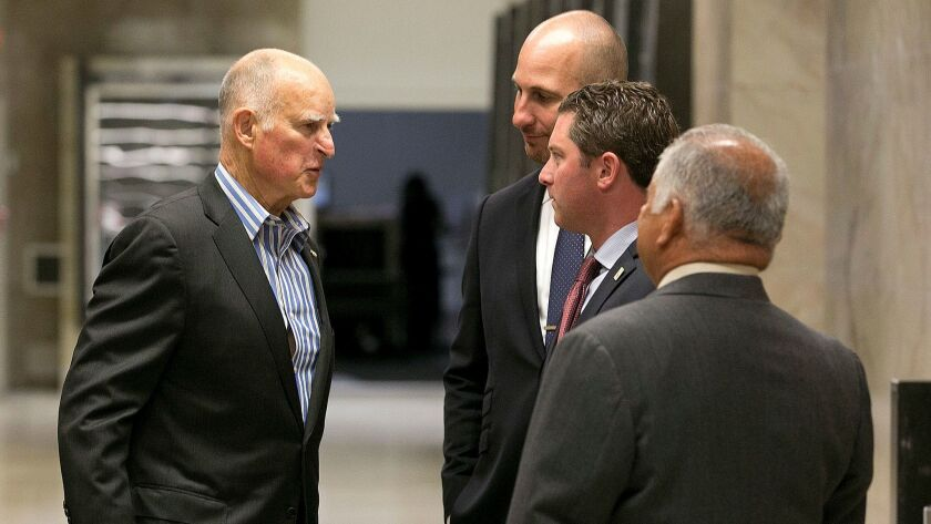 Gov. Jerry Brown, left, chats with Republican Assemblymen Heath Flora of Ripon, Jordan Cunningham of Templeton and Rocky Chavez of Oceanside on July 17. They were among eight Republicans who voted with Democrats to extend the cap-and-trade program.