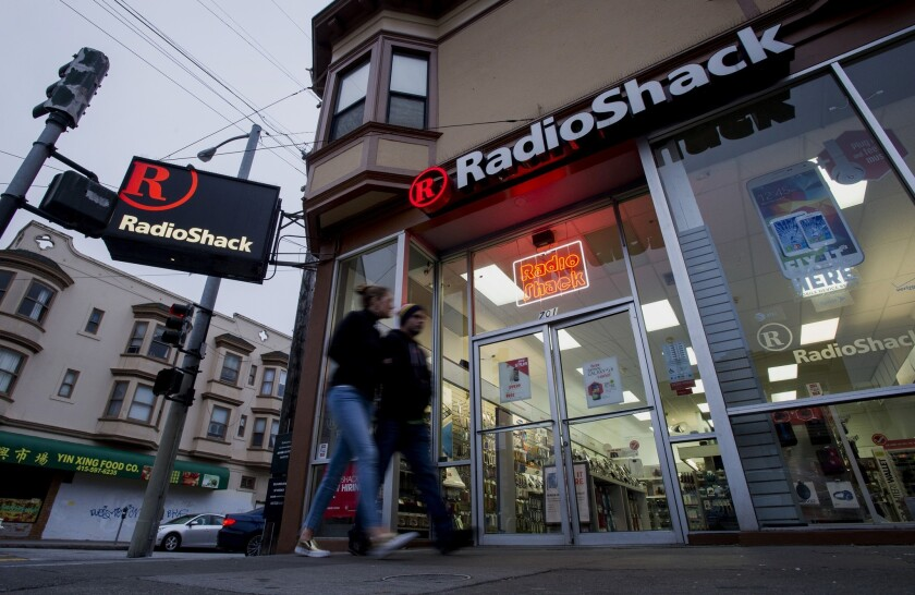 RadioShack continues to struggle in its turnaround efforts. The Texas company on Tuesday reported its ninth consecutive quarterly loss. Above, pedestrians walk past a RadioShack outlet in San Francisco last week.