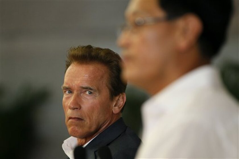 California Gov. Arnold Schwarzenegger, left, looks at China's Ministry of Railways Vice Minister Lu Chunfang, right, speaking Sunday, Sept. 12, 2010 at Hongqiao Railway Station in Shanghai. (AP Photo/Eugene Hoshiko)