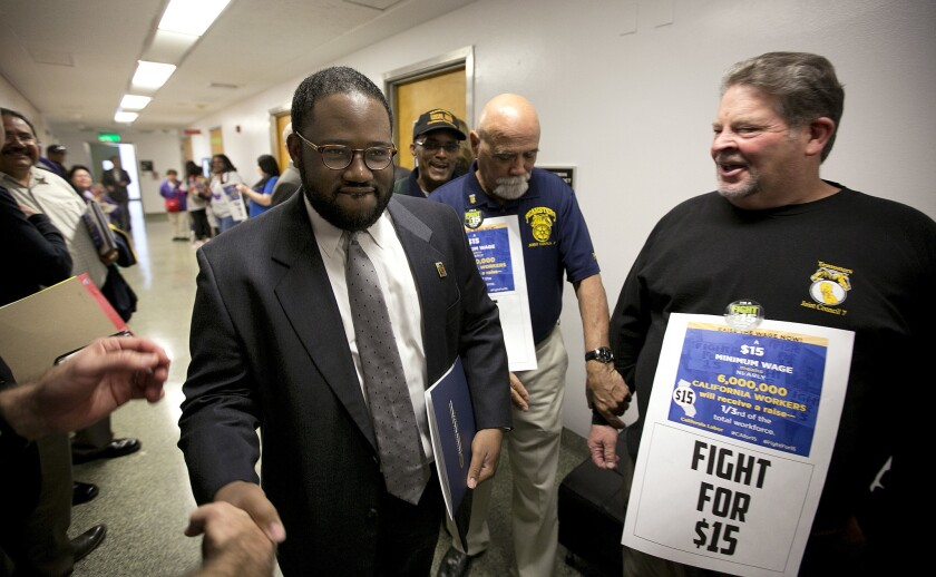 Assemblyman Sebastian Ridley-Thomas is greeted by supporters of a measure to raise the state's minimum wage.