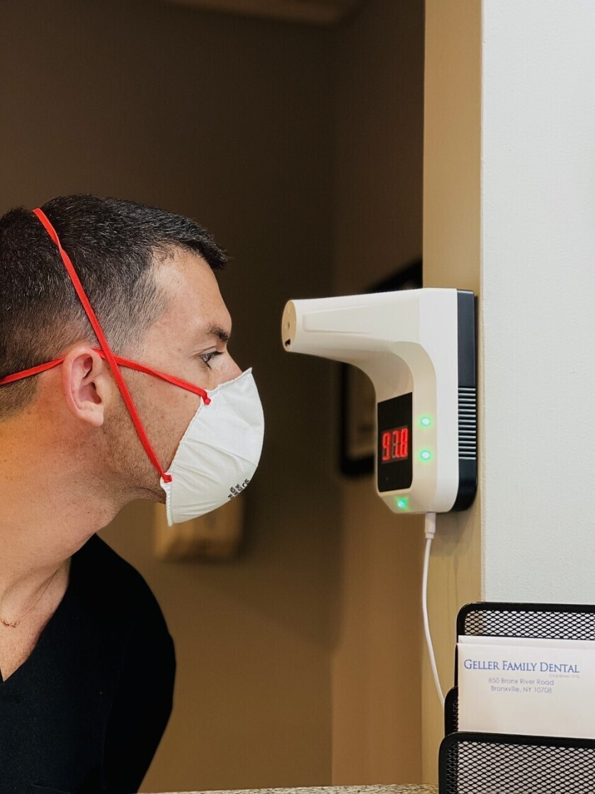 In this photo provided by Geller Family Dental, Dr. Andrew A. Geller, general and cosmetic dentist at Geller Family Dental has his temperature taken at the entry to his office on Thursday, Feb. 4, 2021, in Bronxville, N.Y. As more coronavirus vaccine doses become available, many business owners face a difficult decision: whether to require employees to be inoculated. Geller initially didn't feel comfortable with requiring his staff to get the shots because of the many unknowns about the vaccine. But he did extensive research and concluded that the 23 employees at Geller Family Dental should be vaccinated. (Constantine Venetopoulos/Geller Family Dental via AP)