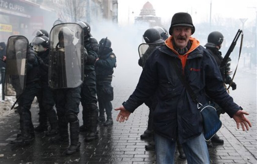 A man reacts as he stands in front of riot police at Lithuania's Parliament building in Vilnius, Friday, Jan. 16, 2009. Police used tear gas and rubber bullets to disperse anti-government protesters throwing rocks and eggs at Lithuania's Parliament on Friday. About a dozen windows on the parliament