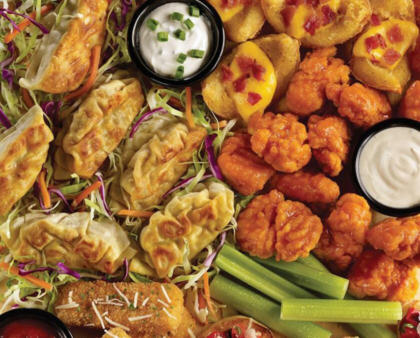 TGIFridays launched endless appetizers Monday. Shown is a selection of the available appetizers and starters, including pot stickers, potato skins and boneless Buffalo wings.