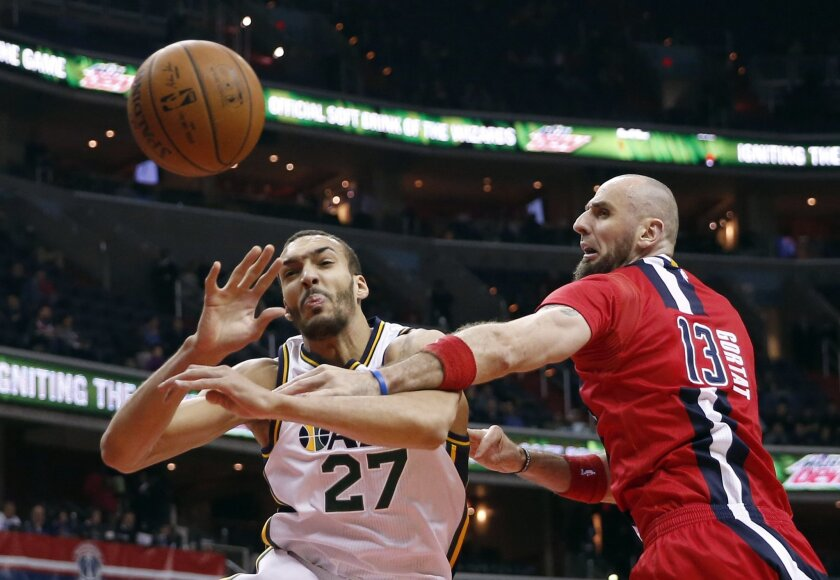 Utah Jazz center Rudy Gobert (27), from France, and Washington Wizards center Marcin Gortat (13), from Poland, get tangled up as they go for a rebound during the first half of an NBA basketball game Thursday, Feb. 18, 2016, in Washington. (AP Photo/Alex Brandon)