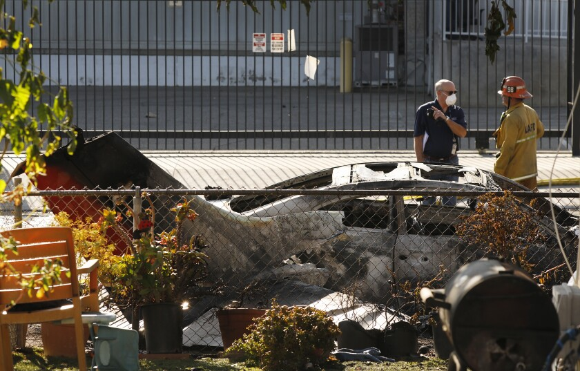 Los Angeles City Fire put out a fire after a small plane crashed into vehicles parked on Sutter Street in Pacoima