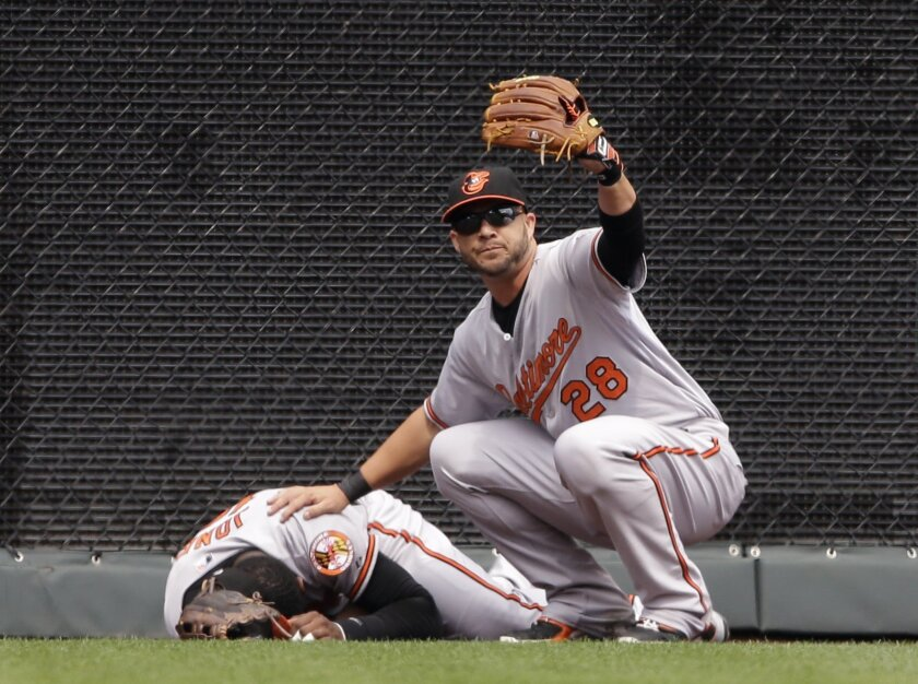 Baltimore Orioles left fielder Steve Pearce (28) calls for help after center fielder Adam Jones, left, hit the wall while chasing a fly ball during the first inning of a baseball game against the Kansas City Royals at Kauffman Stadium in Kansas City, Mo., Thursday, Aug. 27, 2015. (AP Photo/Orlin Wagner)