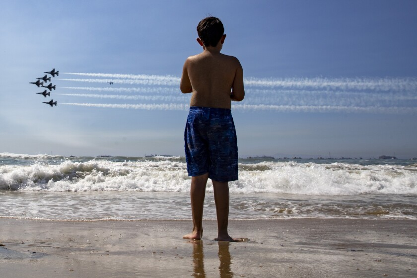 HUNTINGTON BEACH, CA - October 01 2021: Uri Anival, 7, watches as the U.S. Air Force Thunderbirds steak across the sky during the Pacific Airshow on Friday, Oct. 1, 2021 in Huntington Beach, CA. (Brian van der Brug / Los Angeles Times)