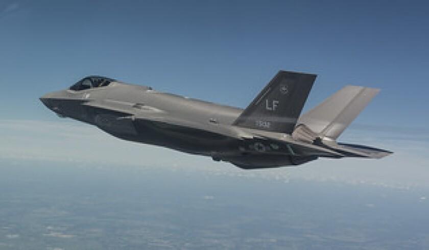 A Lockheed Martin F-35 Lightning II, with components built in Huntington Beach, flies overhead.