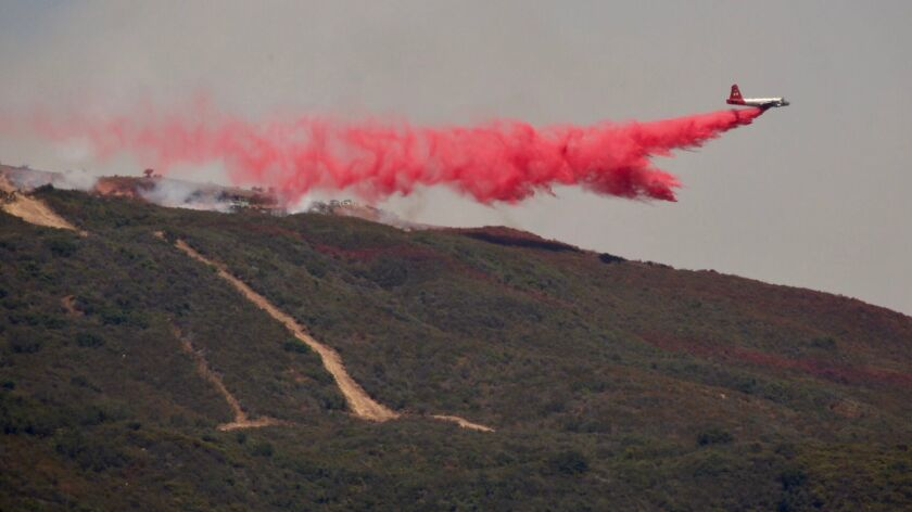 A plane drops red fire retardant on a wildfire