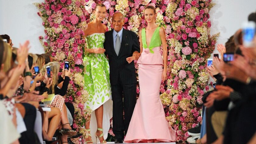 Designer Oscar de la Renta takes a bow with models Karlie Kloss, left, and Daria Strokous after his spring 2015 collection is modeled during Fashion Week in New York.