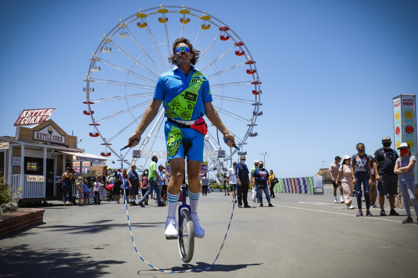 Unicyclist Mark Wilder entertains fair goers by jumping rope on his unicycle at  HomeGrownFun