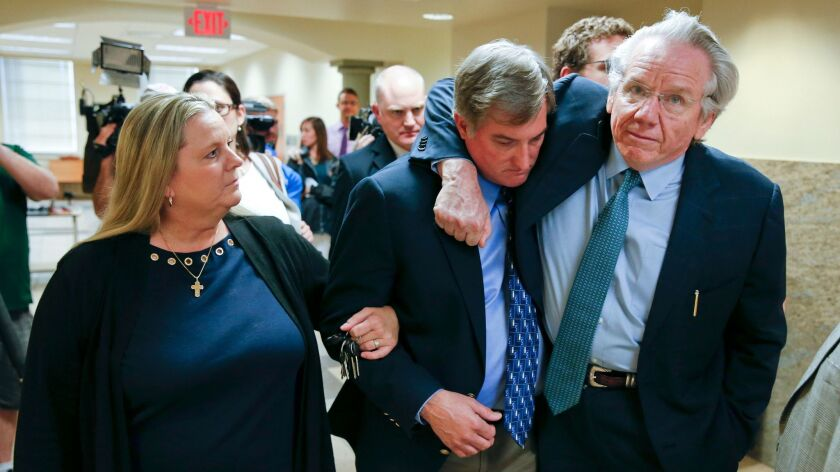 Shannon Kepler, center, walks with his wife, Gina and attorney, Richard O'Carroll, after a hung jury verdict was announced Friday in Tulsa, Okla.