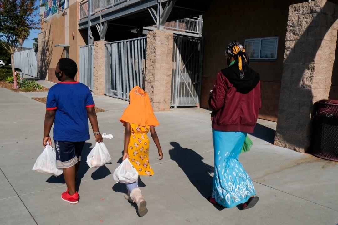 Musa, Osman, 10, and Sadiya, 7, walk to a San Diego Unified School District campus down the street