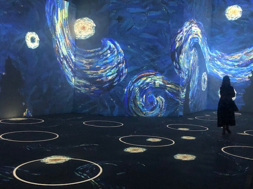A person stands in a room with walls with blue swirls of paint and a floor with outlined white circles.