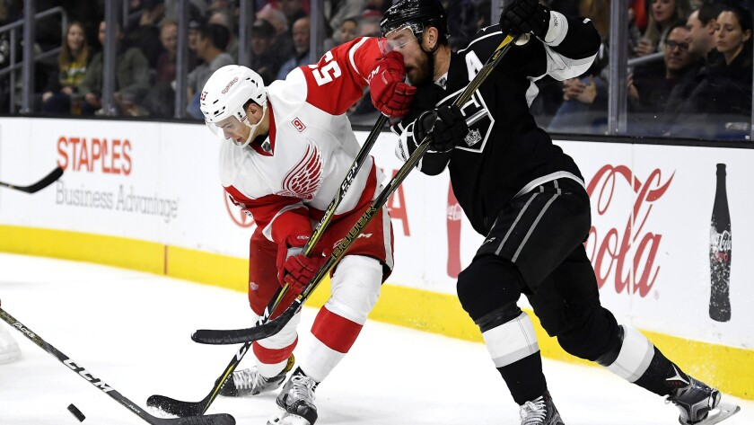 Kings center Jeff Carter, right, takes a shot to the face from Red Wings defenseman Alexey Marchenko.