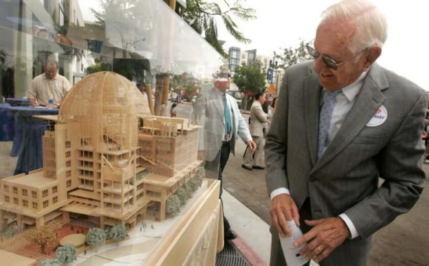 John McAllister, president of The Friends of the San Diego Public Library looks at a model of the library before the start of the groundbreaking ceremony in East Village.