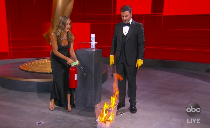 In this video grab captured on Sept. 20, 2020, courtesy of the Academy of Television Arts & Sciences and ABC Entertainment, Jennifer Aniston, left, and Jimmy Kimmel sanitize the winner's envelope while presenting the award for outstanding lead actress in a comedy series during the 72nd Emmy Awards broadcast. (The Television Academy and ABC Entertainment via AP)
