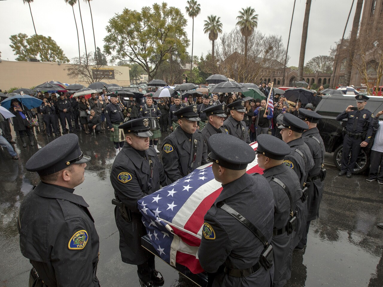 People stand in rain as Pomona Police Officer Greggory Casillas's funeral procession leaves Purpose Church for internment.
