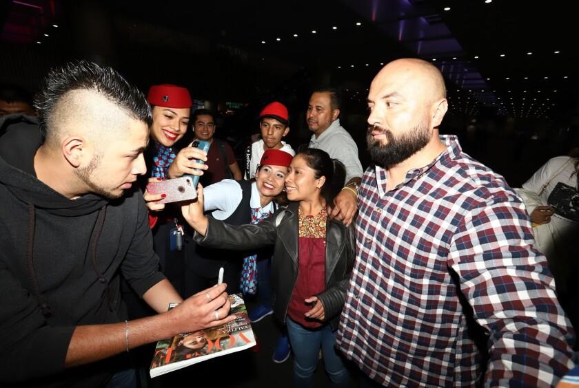 Procedente de Los Ángeles, California, la oaxaqueña Yalitza Aparicio (izq.) era esperada por algunos fans con quienes se tomó fotos y firmó revistas.