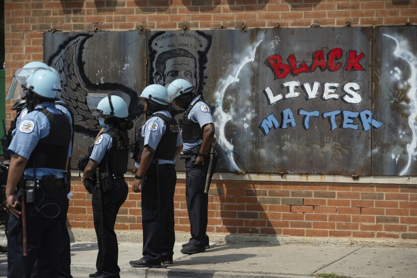 Police officers stand beside a mural for George Floyd