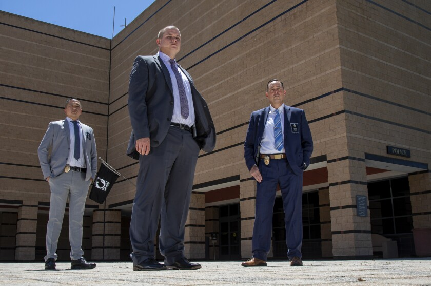 Three men in suits and ties, with badges on their belts, pose for a photo in front of a building.