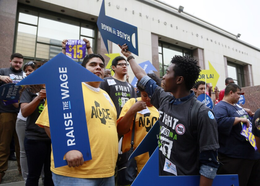 Workers hold a rally in support of the Los Angeles County Board of Supervisors' proposed minimum wage ordinance in July.