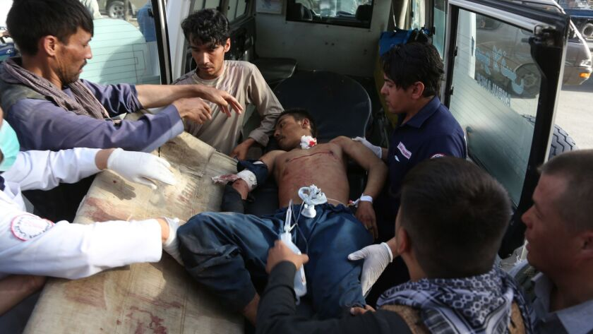 A man is helped into an ambulance after being injured in a deadly suicide bombing that targeted a tr