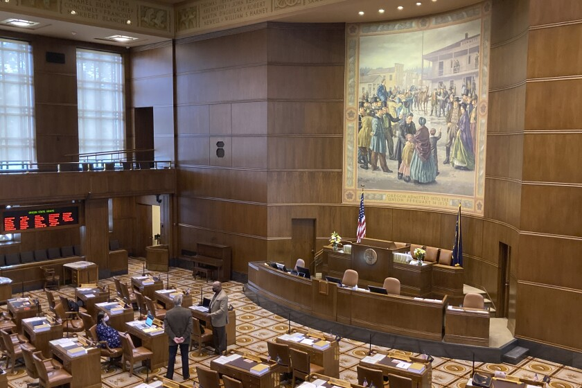 A handful of senators talk on the floor of the Oregon State Senate on Monday, Sept. 20, 2021, as the Oregon Legislature conducted a special session to consider redistricting. The aim of the session is to pass new legislative and congressional district maps which the state will use for elections. (AP Photo/Andrew Selsky)