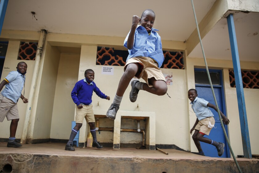 FILE - In this Monday, Oct. 12, 2020 file photo, schoolchildren joke around and play at the Olympic Primary School in Kibera, one of the capital Nairobi's poorest areas, as schools partially re-opened to allow those students due for examinations which had been postponed to prepare, in Kenya. As schools reopen in some African countries after months of lockdown, relief is matched by anxiety over everything from how to raise tuition fees amid the financial strain wrought by the COVID-19 pandemic to how to protect students in crowded classrooms. (AP Photo/Brian Inganga, File)