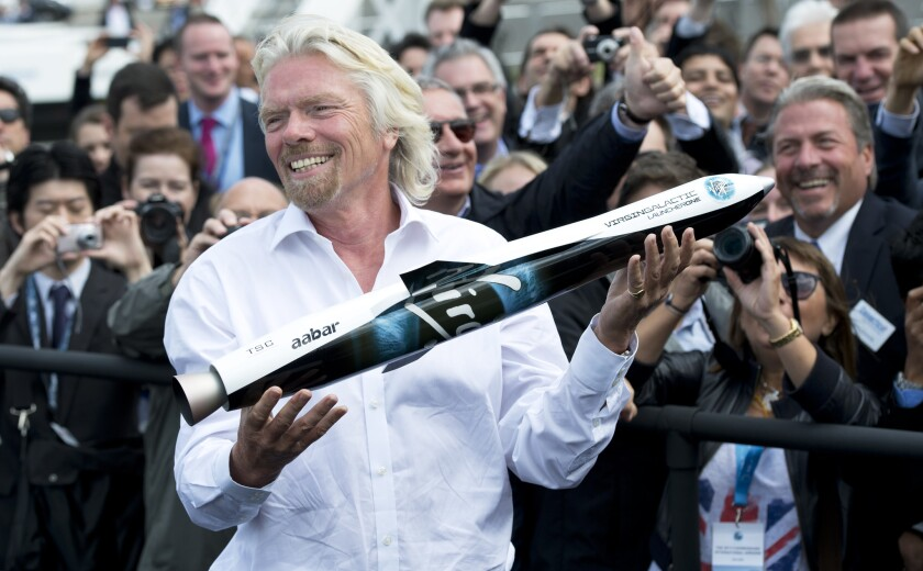 Virgin Galactic founder Richard Branson shows a model of LauncherOne to the crowd at the Farnborough International Airshow in Hampshire, England, on July 11, 2012. LauncherOne is designed to deliver small satellites into orbit.