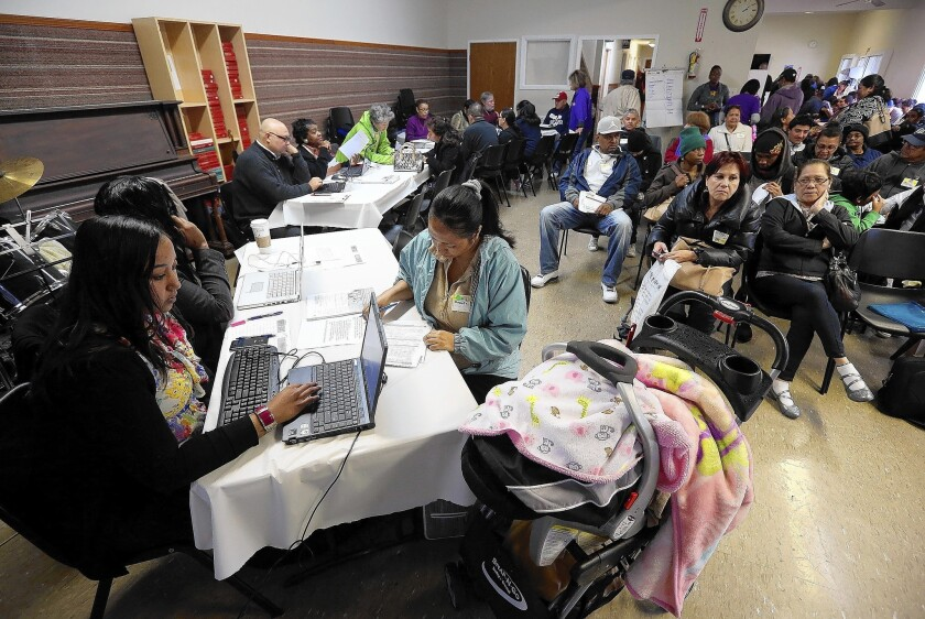 Workers help applicants register for healthcare insurance during an enrollment fair at the Bay Area Rescue Mission in Richmond, Calif.