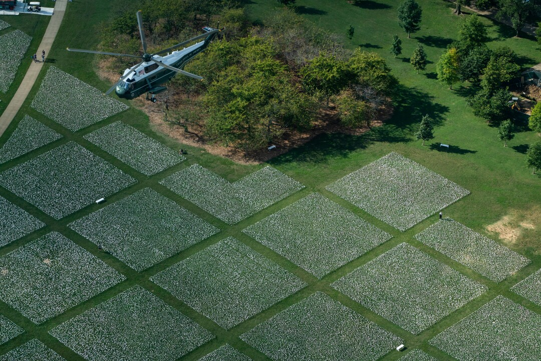 A helicopter flies over white squares on a green lawn