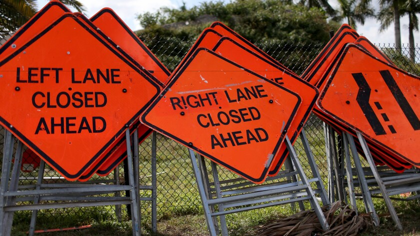 Construction work signs are stacked against a fence in Florida