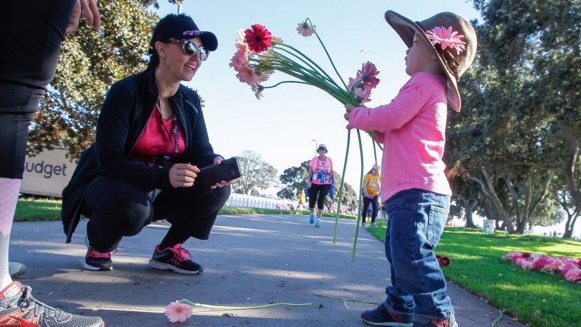 Archer Steed (right), 2, offers a Gerbera daisy to walker Toni Van Valkenburg during the Susan G. Komen 3-Day on Saturday at Bonita Cove on Mission Bay in San Diego. Dramm and Echter, a flower farm in Encinitas, donated 10,000 Gerbera stems to the walk.