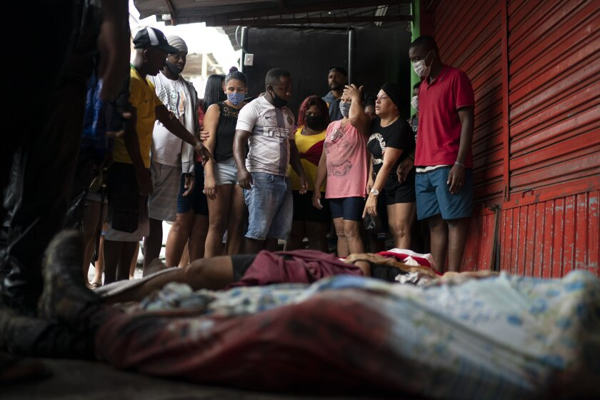 FILE- In this May 15, 2020 file photo, residents look at bodies of people who died amid an armed confrontation, after the bodies were brought from inside the Alemao slum complex to one of the slum's entrances in Rio de Janeiro, Brazil. More than 600 people were killed by police in the state of Rio de Janeiro in the first months of this year. That's about double the number of people killed by police over the same period in the entire U.S., which has 20 times Rio's population. (AP Photo/Leo Correa, File)