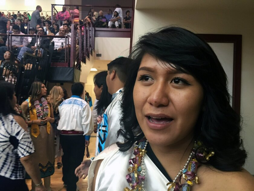 Feather Alcott of San Ildefonso Pueblo in N.M., awaits the arrival of first lady Michelle Obama and the start of her high school graduation ceremony at the Santa Fe Indian School in Santa Fe, N.M., Thursday, May 26, 2016,  The first lady's visit to Santa Fe marks the second of three commencement ad