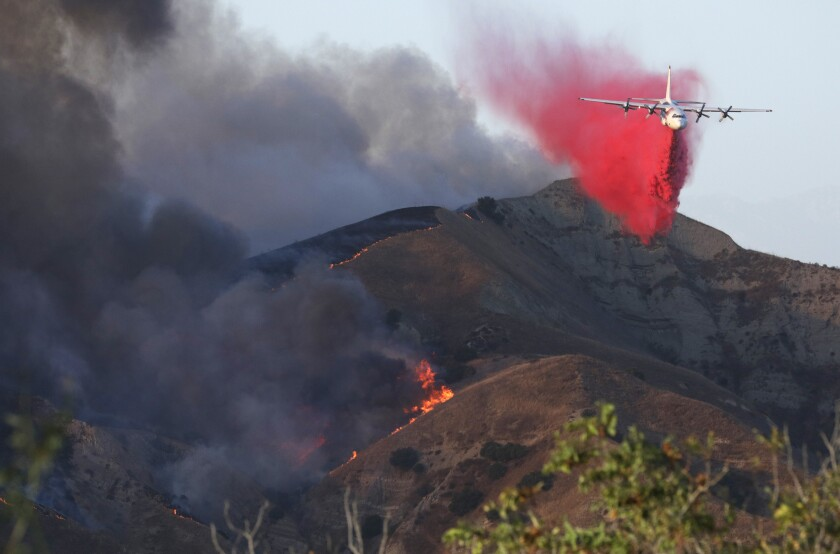 An air tanker drops fire retardant drop on a mountain ridge.