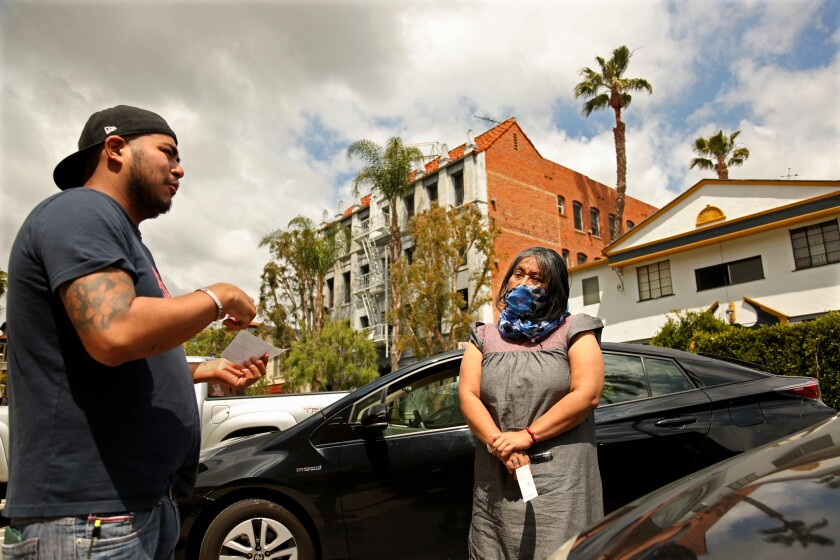 Odilia Romero talks with Francisco Vasquez Gonzalez, 31, from Oaxaca, Mexico, after giving him a relief check. Vasquez lost his jobs as a cook at two Century City restaurants.