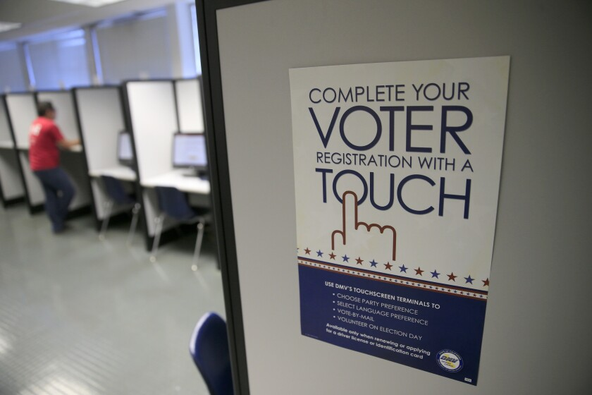 A sign advertises a touch-screen machine for voter registration at the Department of Motor Vehicles in Santa Ana, Calif.