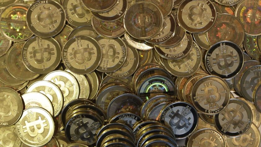 FILE - This April 3, 2013file photo shows bitcoin tokens at 35-year-old software engineer Mike Cald