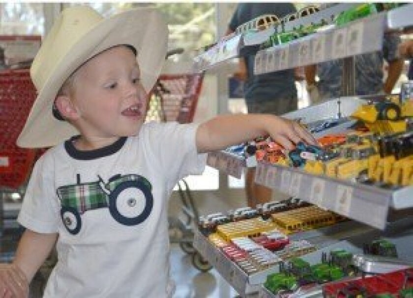 Dawson Schuler, 3, finds a forklift among the miniature farm equipment models in the new Tractor Supply company store. Sentinel photo/Karen Brainard
