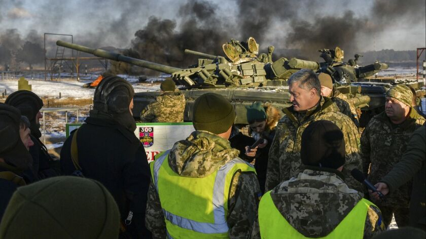 Ukrainian President Petro Poroshenko, second from right, speak with soldiers during a military train