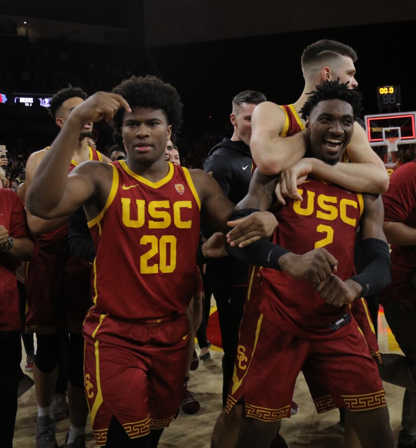 LOS ANGELES, CA - MARCH 7, 2020: USC Trojans guard Jonah Mathews (2) is swarmed by teammates USC Trojans guard Ethan Anderson (20) and USC Trojans forward Nick Rakocevic (31) after scoring the game winning 3-point shot to beat UCLA in the final moments at Galen Center on March 7, 2020 in Los Angeles, California. (Gina Ferazzi/Los AngelesTimes)