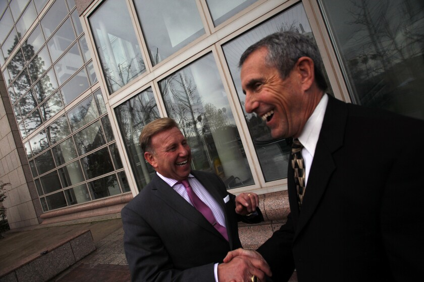 Superior Court Judge Craig Richman, right, shakes hands with his lawyer, James Blatt, left, outside