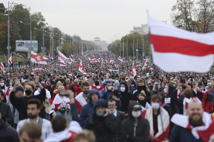 A sea of people with red and white flags fill a street in protest