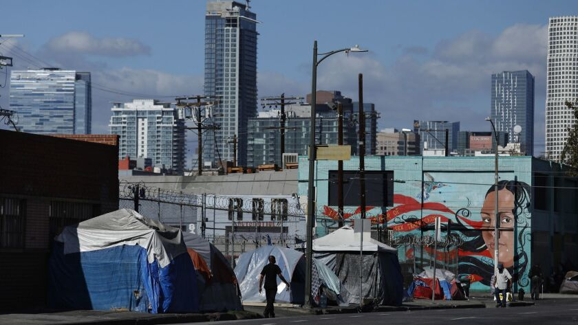 LOS ANGELES, CA-OCTOBER 11, 2018: People walk past a homeless encampment on 6th St., just west of Ce