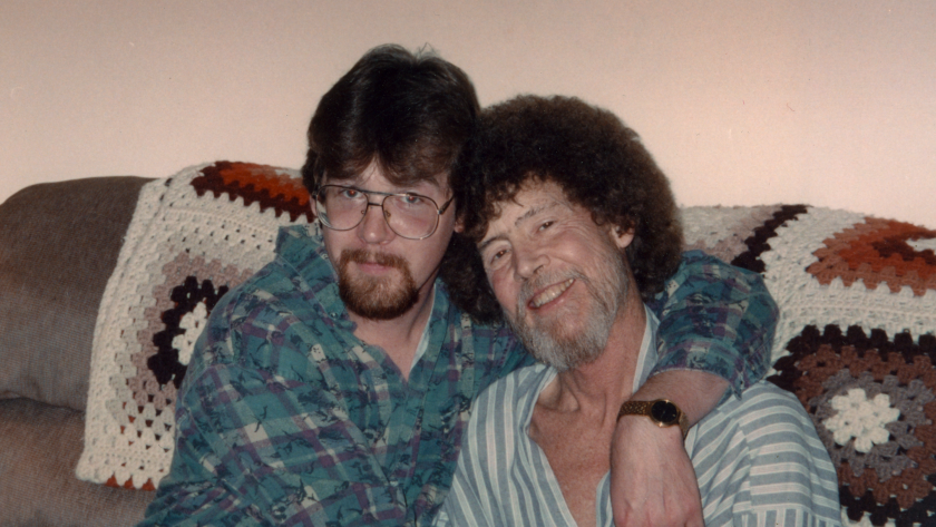 """An adult son with his arm around his father in the documentary """"Bob Ross: Happy Accidents, Betrayal & Greed."""""""