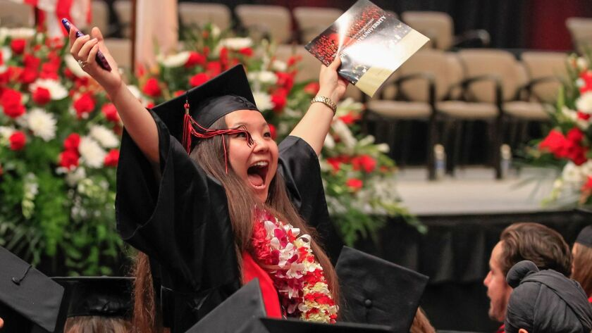 Noelle Green waves to family and friends before College of Arts and Letters graduation at SDSU