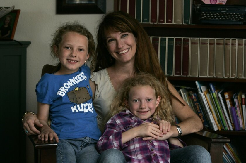 """Tammy Greenwood with her daughters Mikaela, left, and Esmee in their home. """"When I look back, this year will stick out in my mind,"""" Greenwood said."""